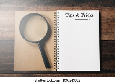 magnifying glass and notebook with TIPS AND TRICKS word with copy space on wooden table. tips and tricks concept