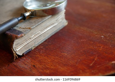 Magnifying glass and old book. Retro stylized photo. Selective focus