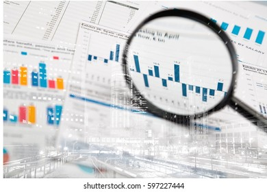 Magnifying glass on business graphs and charts.