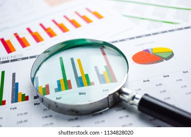 Magnifying glass on Charts Graphs spreadsheet paper. Financial development, Banking Account, Statistics, Investment Analytic research data economy, Stock exchange trading, Business office concept.