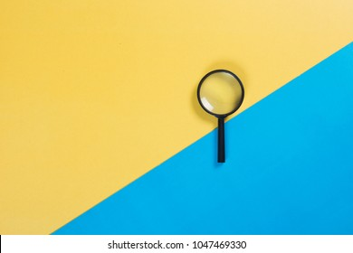 magnifying glass on color background