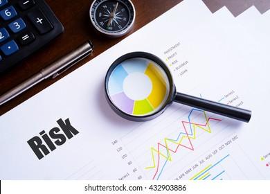 """Vergrootglas op kleurrijk taartdiagram met """"Risk"""" tekst op papier, dobbelstenen, bril, pen, laptop calculator op houten tafel - business, banking, finance en investment concept"""