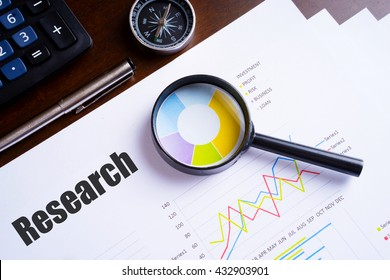 "Magnifying glass on colourful pie chart with ""Research"" text on paper, dice, spectacles, pen, laptop calculator on wooden table - business, banking, finance and investment concept"