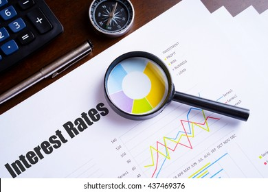 """Magnifying glass on colourful pie chart with """"Interest rates"""" text on paper, dice, spectacles, pen, laptop calculator on wooden table - business, banking, finance and investment concept"""