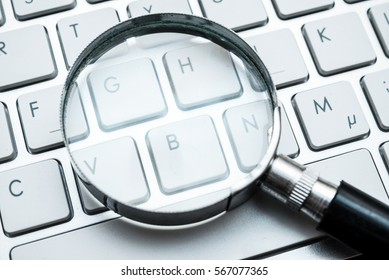 Magnifying glass on a computer keyboard. Internet search and keywords concept