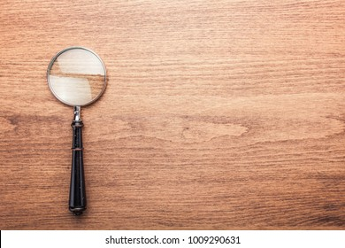 Magnifying glass on the dark brown wooden background