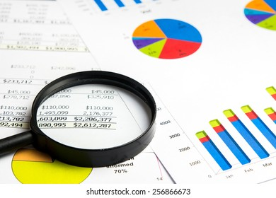 magnifying glass on financial chart documents