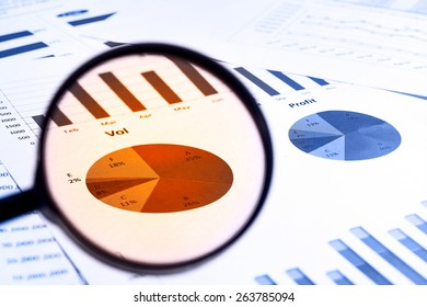 magnifying glass on financial report documents