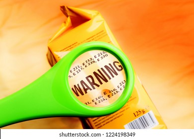 Magnifying glass on food additives label with word warning. Concept warning food additives. Reading ingredients list on food package with magnifying glass.