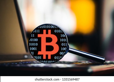 Magnifying glass on laptop keyboard. Internet security blue binary zero one code with red bitcoin sign background.