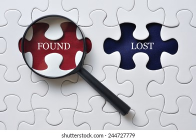 """Magnifying Glass On Missing Puzzle with """"FOUND/LOST"""" Word, Antonym Concept and Selective Focus"""