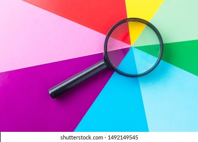 Magnifying glass on multi-colored sheets of paper. Search for diversity color combinations. The concept of finding a variety of choices.