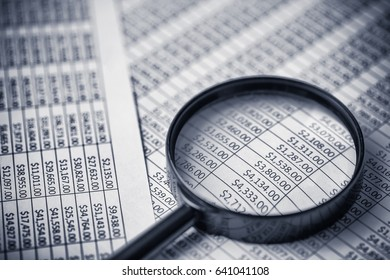 Magnifying glass on paper money dollars report.