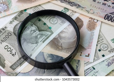 Magnifying glass on pile of asian leading country new emerging market money banknotes, indian rupee, chinese yuan and japanese yen, searching for yield or financial concept.