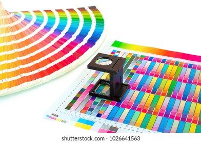 Magnifying glass on printed color swatch isolated on white. Color management in printing process with magnifying glass and paint guide.  Color selection Pre-Press concept. Loupe and a ink sampler.