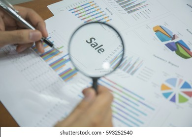"""Magnifying glass on """"Sale"""" text on chart on the desk, finance and investment concept."""