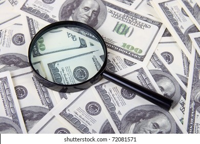 Magnifying glass on a stack of dollars