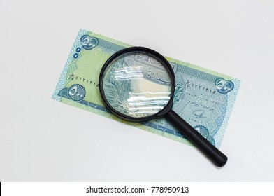 magnifying glass on uncirculated iraqi dinar (IQD) isolated on white