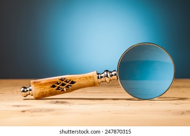 magnifying  glass  on wooden table and blue background
