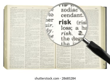 A magnifying glass on the word RISK on a dictionary.