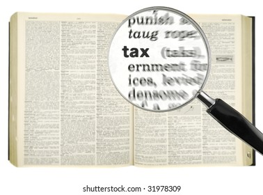 A magnifying glass on the word TAX on a dictionary. Isolated on white.
