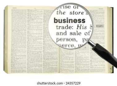 A magnifying glass on the world BUSINESS on a dictionary.