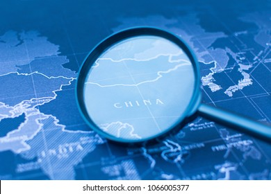 Magnifying glass on the world map selective focus of China, war concept.