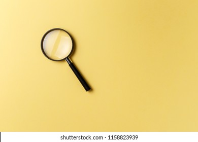 Magnifying glass on yellow background. Top view. Flat lay. Copy space. Concept
