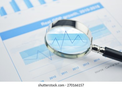Magnifying glass over financial chart and graph business, analysis concept