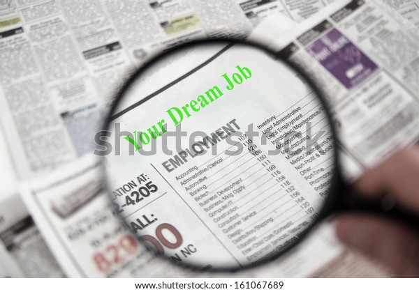 Magnifying glass over a newspaper classified section, with Your Dream Job text