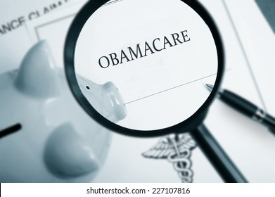 Magnifying glass over Obamacare policy and piggy bank