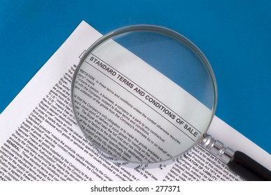 """Magnifying glass over """"Standard Terms and COnditions"""" of a contract."""