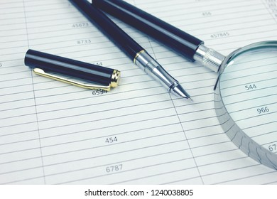 Magnifying glass with pen and document on the desktop