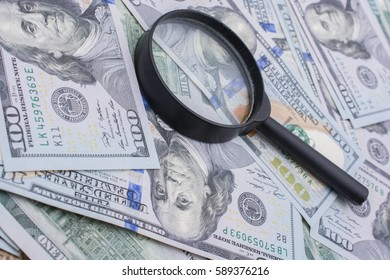 Magnifying glass is placed over  of US dollar the banknotes