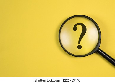 Magnifying glass with QUESTION MARK in focus on yellow background. concept of search and research.