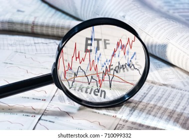 Magnifying glass shows the courses of exchange trade funds, funds and shares