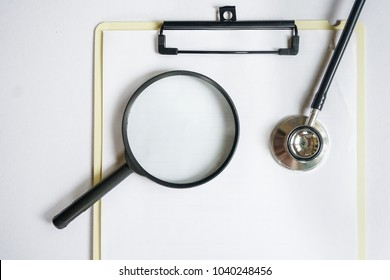 Magnifying glass and stethoscope on medical clip board isolated in white background. Top view