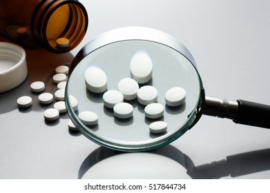 Magnifying glass, tablets and bottle on gray reflection background. Checking ingredients and effectiveness of medicine.