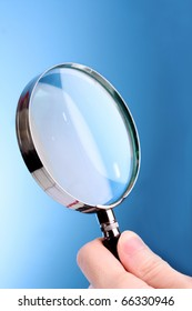 Magnifying glass in woman hand on blue background
