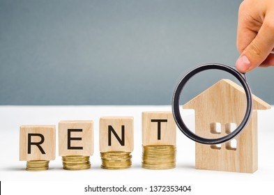 Magnifying glass, wooden blocks with the word Rent, coins and a miniature house. The concept of renting housing and real estate. The cost of a rented home or apartment. Saving money. Rental.