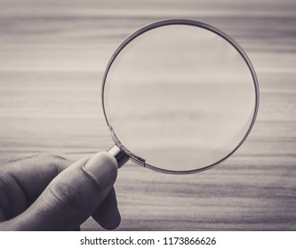 Magnifying glass with the wooden table bakcground.