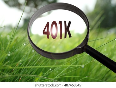 Magnifying glass with the word (401k) pension plan on grass background. Selective focus