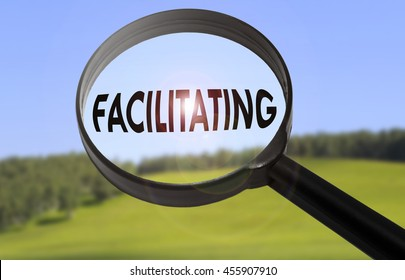 Magnifying glass with the word facilitating on blurred nature background