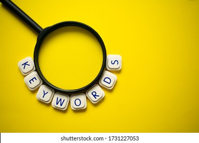 "A magnifying glass and the word ""keywords"" made with letter game blocks surrounding it, on a bright yellow background. Conceptual image of the importance of the keywords in searching engines."