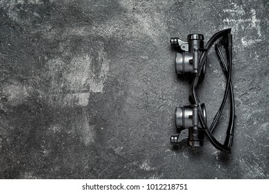 Magnifying LED light glass tool for jeweler or watchmaker on an old rustic cement background, top view with copy space for your text. See better concept.