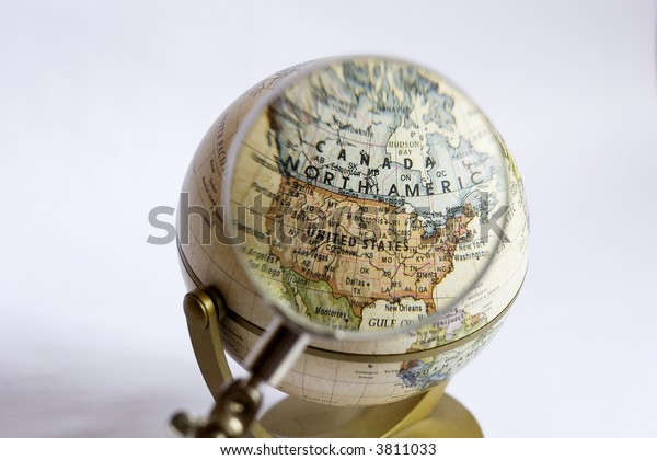 Magnifying lens enlarging and focusing on USA and Canada on a globe