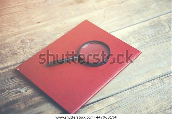 Magnifying lens on folder on wooden table