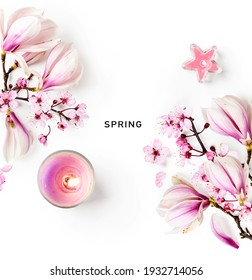 Magnolia and cherry blossom. Creative composition with sakura spring flowers and candles on white background. Springtime layout. Flat lay, top view, floral design. Easter decoration