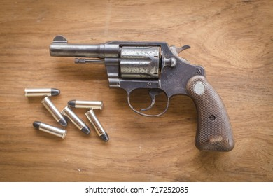 Magnum gun with bullet on wooden background