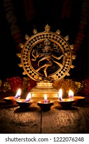 Maha Shivaratri or Diwali concept - Shiva Nataraja figurine with Diwali lights oil ghee candles, India